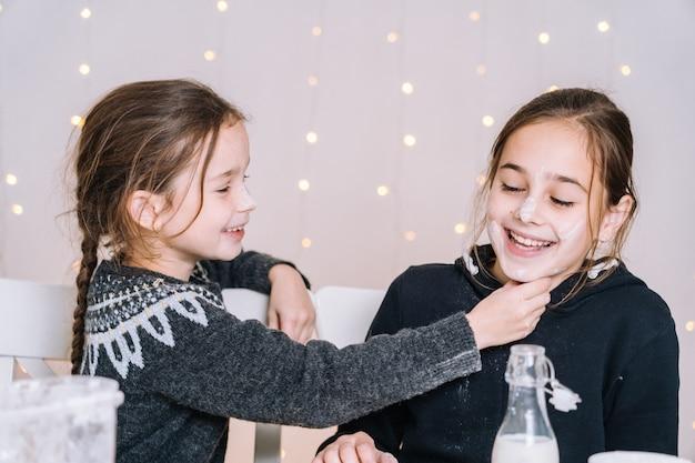 Małe dzieci do pieczenia pierników w domowej kuchni na zimowy dzień. dzieci bawiące się mąką.