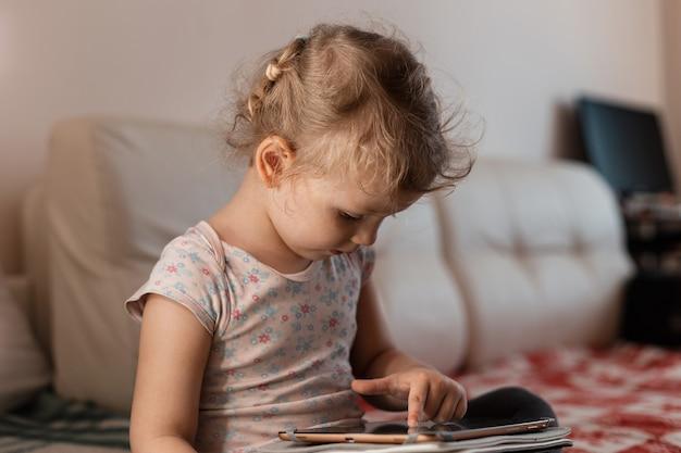 Małe dzieci dziewczynka studiuje i gra na tablecie w pokoju w domu. edukacja izolacyjna i na odległość od najmłodszych lat