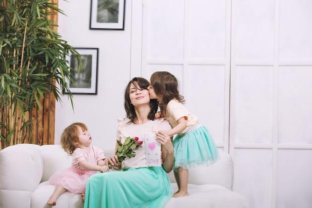 Małe dzieci dziewczynki piękne i urocze dają kwiaty i karty mamy w domu na wakacje
