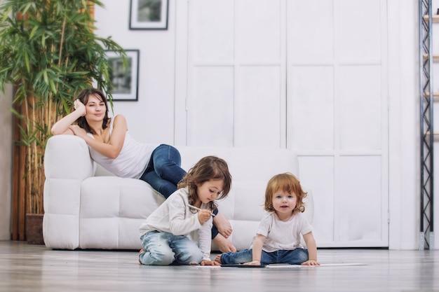 Małe dzieci dziewczynki rysują na podłodze piękne słodkie i zabawne z matką w domu