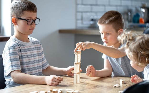 Małe dzieci grają w grę planszową z drewnianymi kostkami w domu w kuchni.
