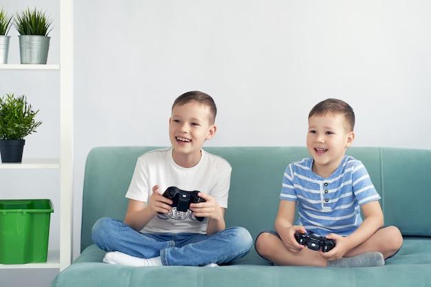 Małe dzieci grają w gry wideo na niebieskiej kanapie.