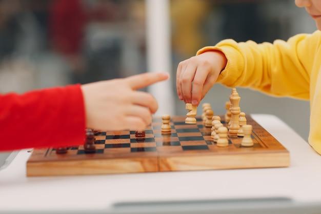 Małe dzieci grają w szachy w przedszkolu lub szkole podstawowej