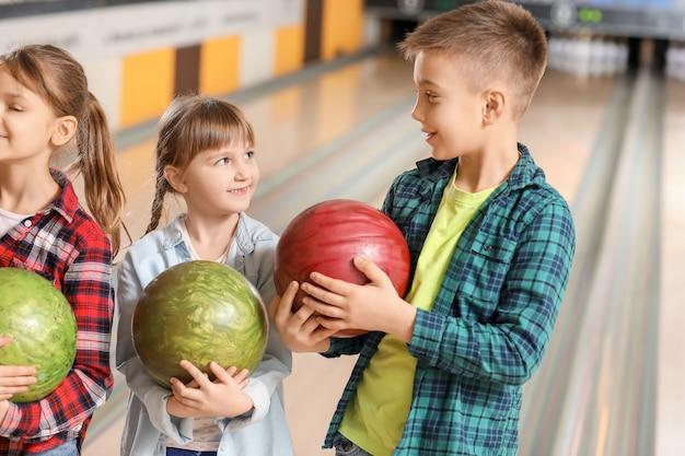 Małe dzieci grające w kręgle w klubie