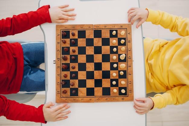 Małe dzieci grające w szachy w przedszkolu lub szkole podstawowej widok z góry