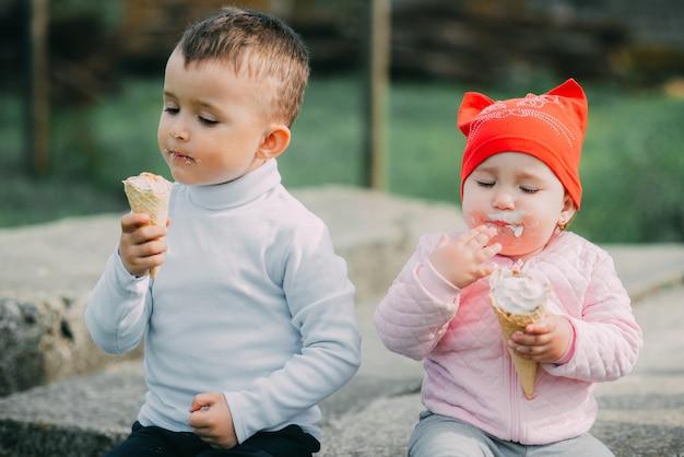 Małe dzieci jedzą lody na świeżym powietrzu w wiosce
