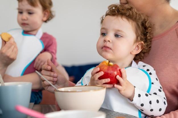 Małe dzieci jedzą obiad w domu