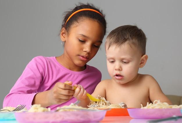 Małe dzieci jedzą spaghetti