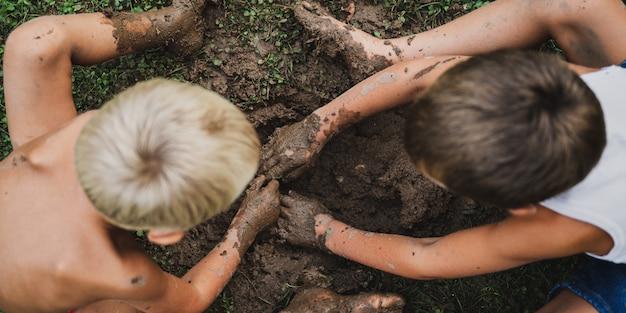 Małe dzieci kopiące błotnistą dziurę