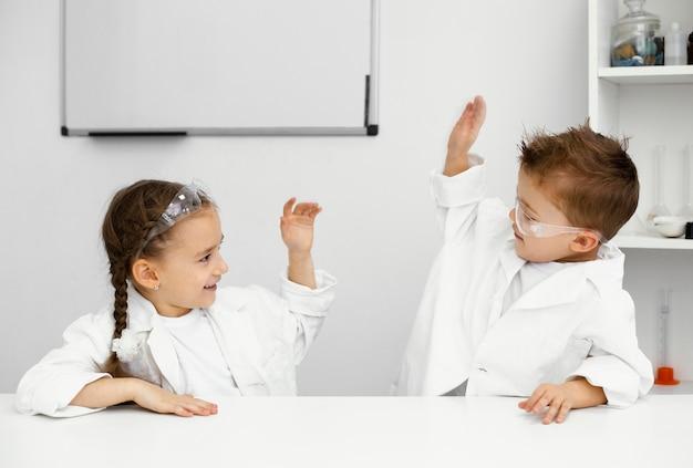 Małe dzieci naukowcy bawią się, przeprowadzając eksperymenty i przybijając sobie piątki