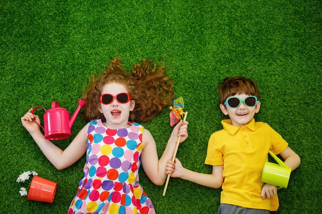 Małe dzieci ogrodnicy leżące na zielonej trawie.