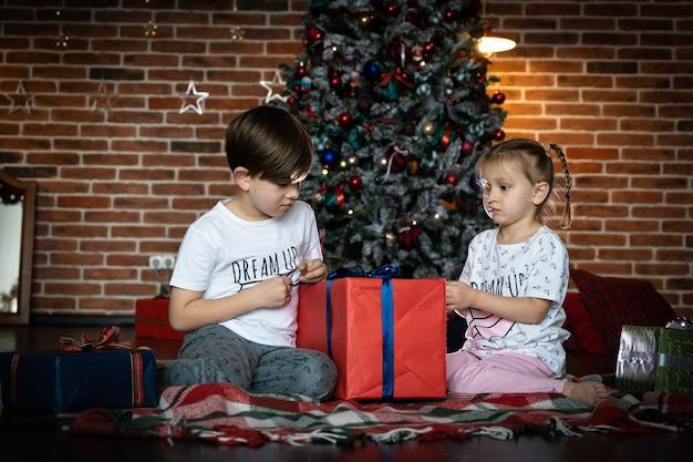Małe dzieci otwierają prezenty obok drzewa i kominka w przytulnym domu z okazji wesołych świąt