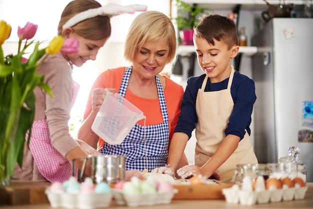 Małe dzieci pomagają babci z ciastem