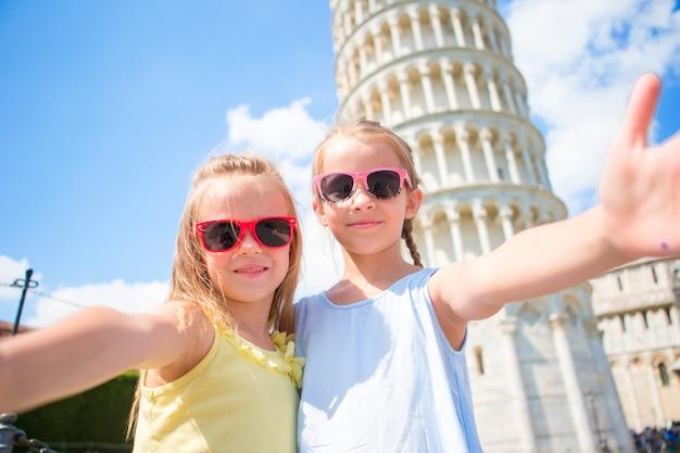Małe dzieci przy selfie tle krzywej wieży w pizie