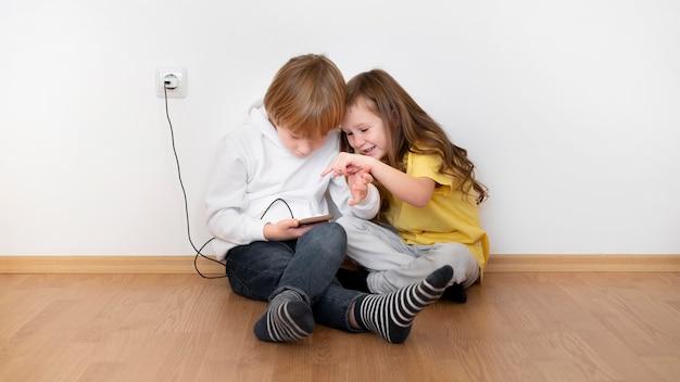 Małe dzieci razem przy użyciu smartfona