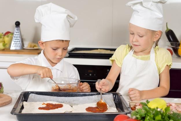 Małe dzieci robią sobie pizzę domowej roboty
