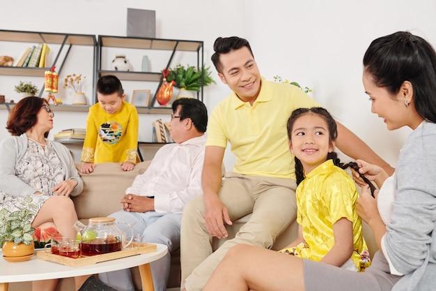 Małe dzieci rozmawiają z rodzicami i dziadkami podczas rodzinnego spotkania w domu
