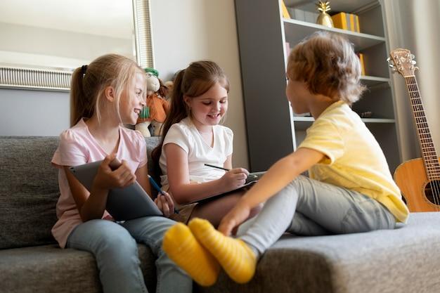 Małe dzieci rysują razem w domu