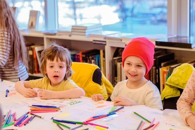 Małe dzieci rysują razem w przedszkolu dziennym
