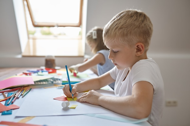 Małe dzieci rysujące ołówkami i markerami przy stole, dzieci w warsztacie. lekcja w szkole artystycznej. młodzi malarze, przyjemne hobby, szczęśliwe dzieciństwo