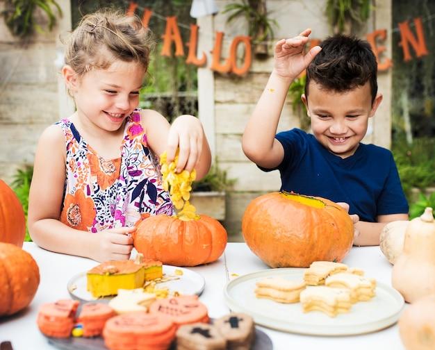 Małe dzieci rzeźbią halloweenowe latarnie