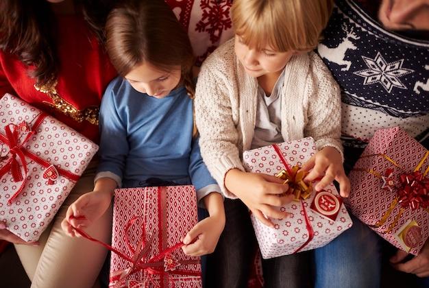 Małe dzieci są gotowe do otwarcia prezentów świątecznych