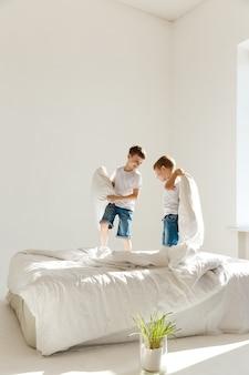 Małe dzieci skaczą na łóżku i bawią się w słońcu walcząc z poduszkami.