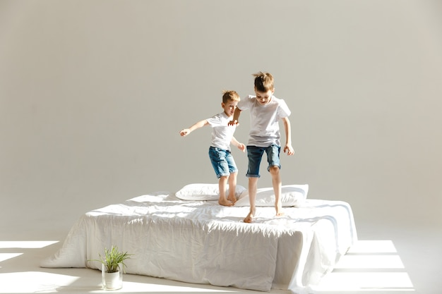 Małe dzieci skaczą na łóżku i bawią się w słońcu.