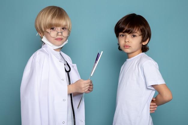 Małe dzieci słodkie urocze, patrząc na kamery, jeden w białym garniturze lekarza, a drugi w białej koszulce na niebieskiej ścianie