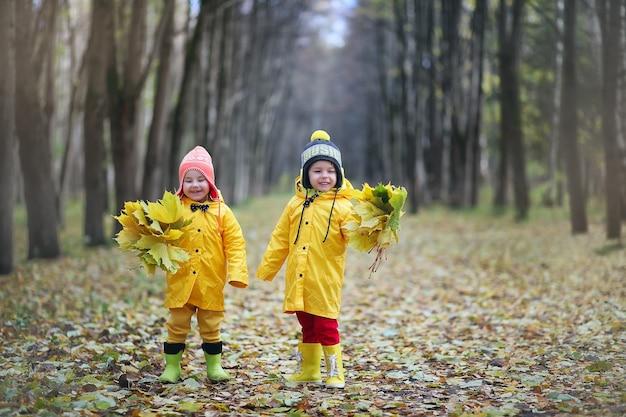 Małe dzieci spacerują po jesiennym parku jesienią liści
