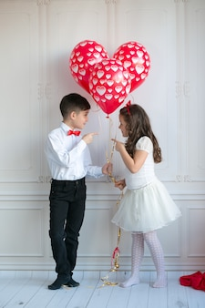 Małe dzieci trzyma i podnosi balony serca. walentynki i koncepcja miłości
