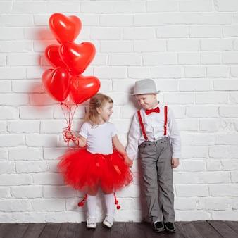 Małe dzieci trzyma i podnosi balony serca. walentynki i miłości pojęcie na białym tle