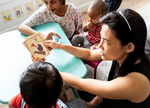 Małe dzieci uczące się angielskiego alfabetu z rodzicami
