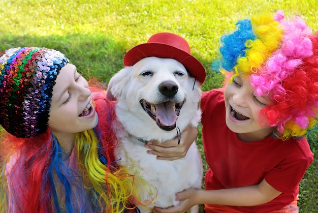 Małe dzieci w eleganckich kombinezonach bawią się z psem na łonie natury.
