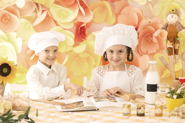 Małe dzieci w formie szefa kuchni przygotują pyszne