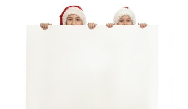 Małe dzieci w świątecznych czapkach trzymających biały plakat