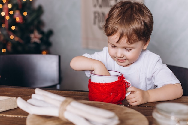 Małe dzieci w świątecznych dekoracjach z herbatą w przytulnym domu z kolorowymi światłami nowego roku