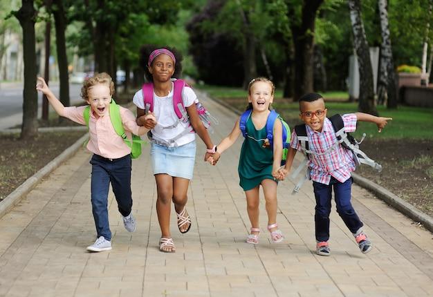 Małe dzieci w wieku szkolnym z kolorowymi tornistrami i plecakami biegną do szkoły. powrót do szkoły