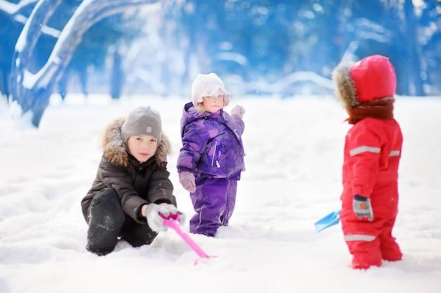 Małe dzieci w zimy ubraniach ma zabawę w parku przy śnieżnym zima dniem. dzieci bawią się na zewnątrz. aktywny na świeżym powietrzu na rodzinne wakacje