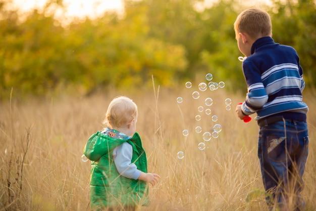 Małe dzieci wpuszczają bańki mydlane do natury
