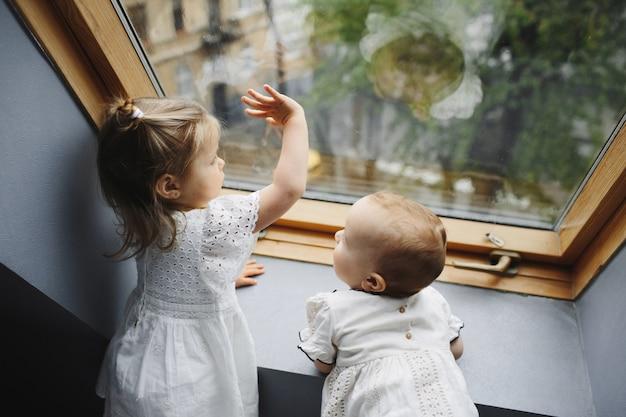 Małe dzieci wyglądają przez okno