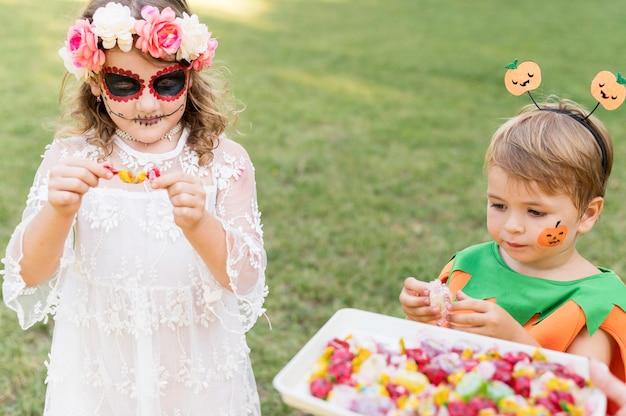 Małe dzieci z kostiumami w parku