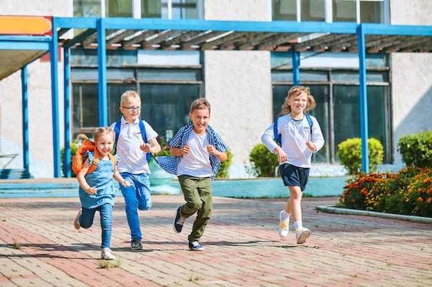 Małe dzieci z plecakami wybiegające ze szkoły