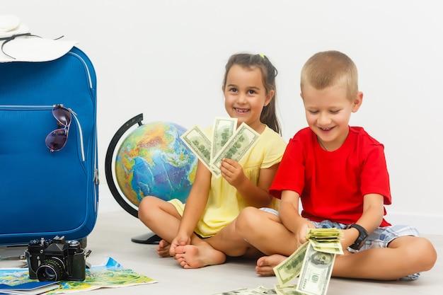 Małe dzieci z walizką stoją razem