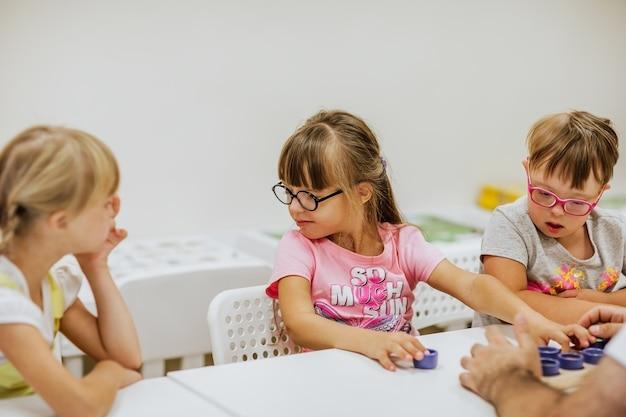 Małe dzieci z zespołem downa uczą się i bawią w pokoju z białymi biurkami