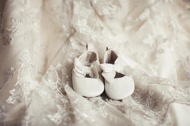Małe dziecięce buty na koronkowej tkaninie