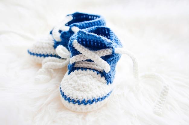 Małe dziecięce buty. ręcznie robione pierwsze trampki dla nowonarodzonego chłopca lub dziewczynki. szydełkowe ręcznie robione trzewiki