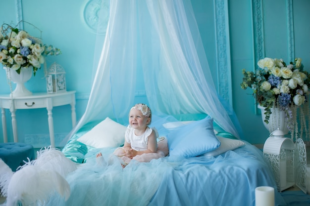 Małe dziecko 1 rok od urodzenia siedzi na łóżku lub krześle w jasnoniebieskim pokoju dziecięcym.