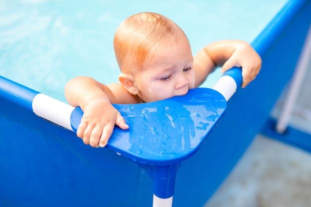 Małe dziecko baw się pluskiem w basenie.