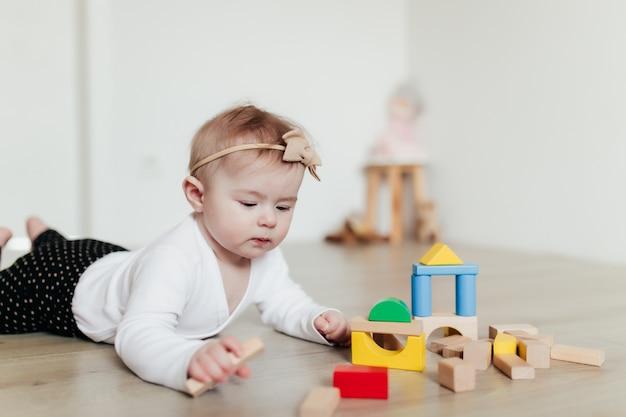 Małe dziecko bawi się kolorowymi drewnianymi klockami konstrukcyjnymi. niewyraźne tło.